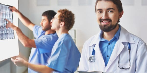 Portrait of friendly doctor looking at camera on background of his colleagues interacting