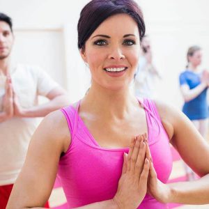 Group of people performing tree-pose yoga exercise in the fitness studio
